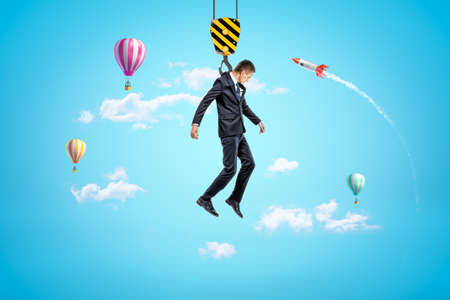 Businessman hanging on construction crane hook with hot air balloons and silver red space rocket in the air on blue background