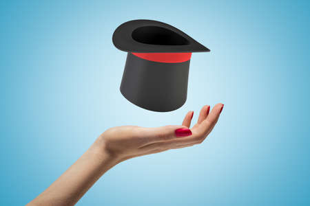 Female hand with black top hat above on blue background Reklamní fotografie