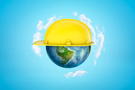 3d rendering of earth sphere with yellow hard hat on blue background Stock fotó