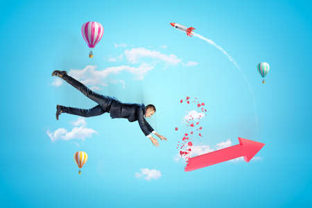Young businessman in sky falling down trying to catch red broken graph arrow, with hot air balloons and rocket in background.