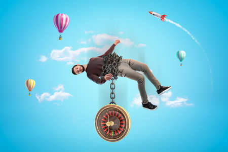 Man in casual clothes chained to roulette with hot air balloons and silver red space rocket in the air on blue background