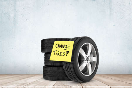 3d rendering of stack of black tires with yellow note saying Change Tires, against concrete wall on wooden floor. Stock fotó