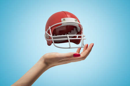 Side closeup of womans hand facing up and levitating small American football helmet on light blue gradient background.