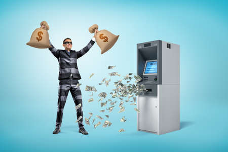 Happy male robber holding money bags with dollars falling out of ATM machine on blue background