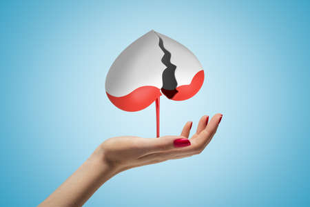 Side view of womans hand facing up and levitating gray broken heart upside down, with red liquid dripping down, on light blue background. Stok Fotoğraf