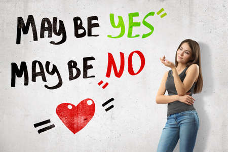 Young thinking brunette girl wearing casual jeans and t-shirt with Maybe yes maybe no sign and cartoon heart on white wall background