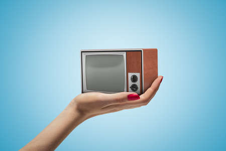 Side closeup of womans hand facing up and holding small retro TV set on light blue gradient background.