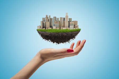 Side closeup of womans hand facing up and levitating small piece of land with modern city on it on light blue background. Stockfoto