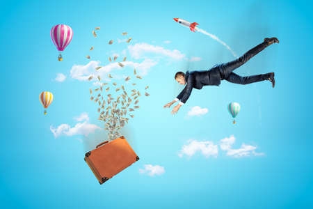 Businessman reaching to brown suitcase with dollars flying out, hot air balloons and silver red space rocket in the air on blue background