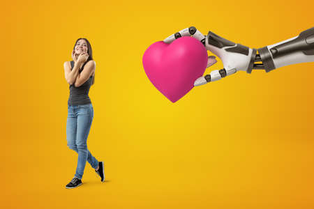 Young happy brunette girl wearing casual jeans and t-shirt and big robotic hand holding pink heart on yellow background