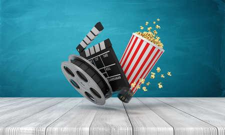 3d rendering of pop corn bucket, film reel, and clapperboard standing on wooden floor near blue wall. Stock Photo