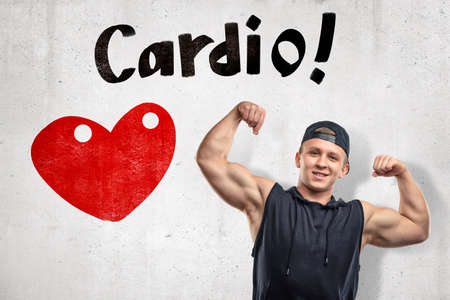 Strong muscular young man showing biceps with big red heart and Cardio sign on white background Stock fotó