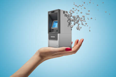 Side closeup of womans hand facing up and holding small ATM which has started to dissolve into pieces on light-blue background.