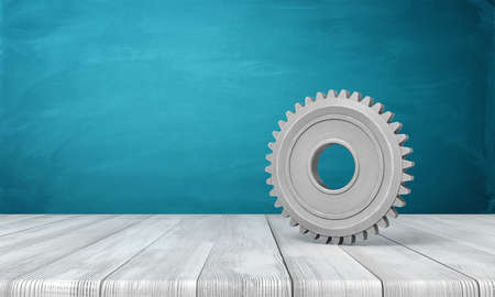 3d rendering of light-grey metal gearwheel standing on wooden floor near blue wall with some copy space on the left. Stock fotó