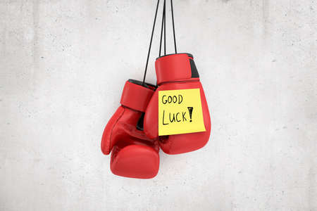 3d rendering of red boxing gloves with yellow Good luck note on white wall background Archivio Fotografico - 134738286