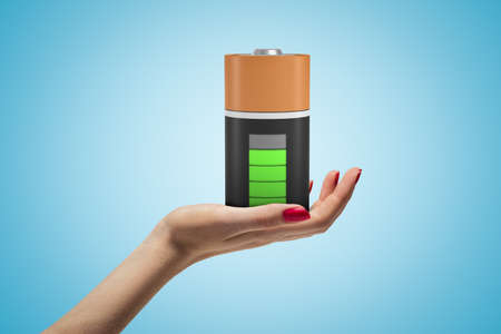 Female hand holding fully charged battery on blue background