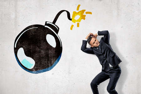 Young businessman protecting his head with his hands and big cartoon ball bomb on white background