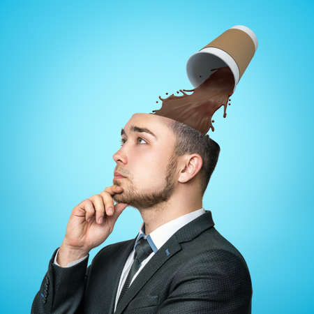 Thinking businessman with paper coffee cup spilling out in his head on blue background