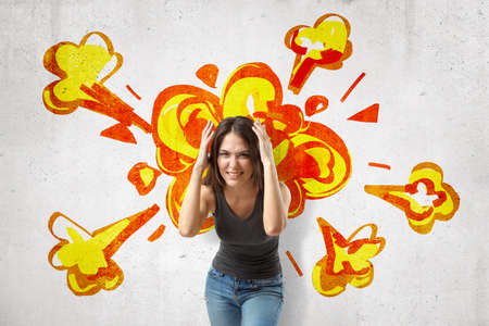 Young brunette woman in casual clothes making brain explosion gesture with cartoon explosion drawn on white wall background Stock Photo