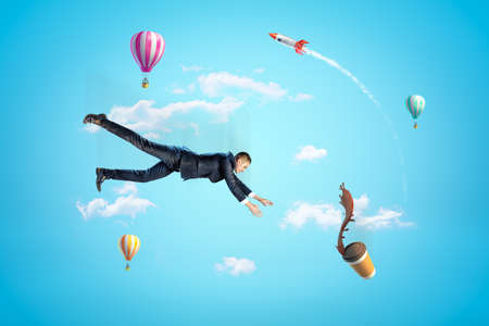 Young businessman in sky falling down trying to catch paper coffee cup which is spilling coffee in air with hot air balloons and rocket in background. Фото со стока