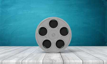 3d rendering of film reel on white wooden floor and dark turquoise background Stock Photo