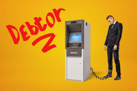 Sad young businessman standing in half-turn chained to ATM on amber background with big red title Debtor.