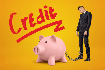 Sad businessman chained to pink piggy bank with Credit sign above on yellow background.