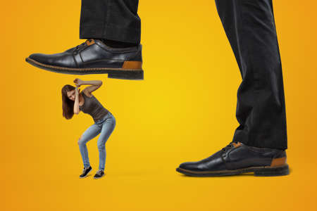 Side close-up of mans feet in shoes, one foot in air ready to step on miniature young girl whos covering her head in fear, on amber background.