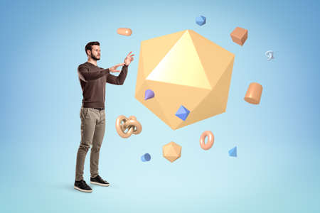 Young man standing and trying to manipulate a huge yellow icosahedron floating in air with lots of other small geometric objects on blue background.