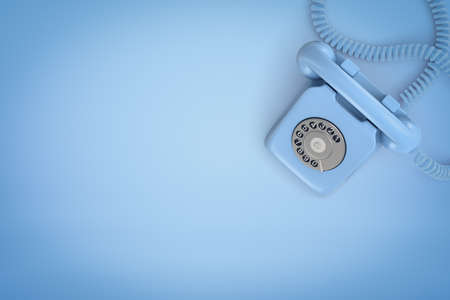 3d rendering of light blue landline phone viewed from above standing on blue background of the same color with lots of copy space.