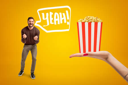 Young man in casual clothes shouting Yeah and holding clenched fists because he is so happy about pop corn box hes neen offered on amber background.