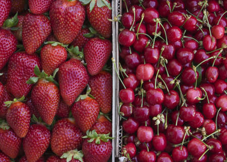 Strawberries and cherries in baskets at the market  photo
