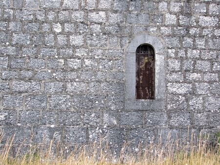 Old construction with grass and window