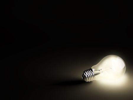 Turned on electric light bulb on black background Stock Photo