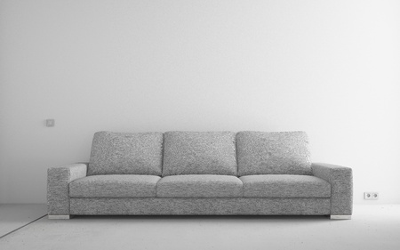 Gray modern sofa in empty room with white walls and concrete floor Stock Photo