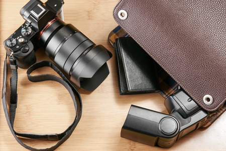 lens unit: Shot of a mirror-less camera and flash unit on a wooden surface