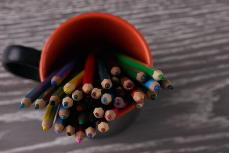 Colorful pencils in a cup on wooden table