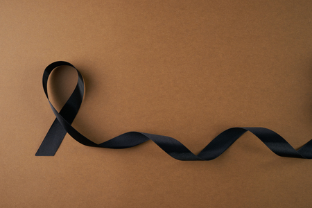 Black awareness ribbon on brown background Фото со стока