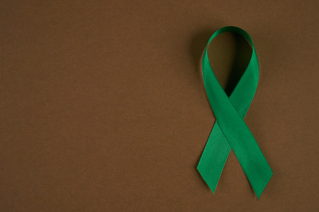 Green awareness ribbon on brown background. Symbol of Mental Health. Top vew with copy space