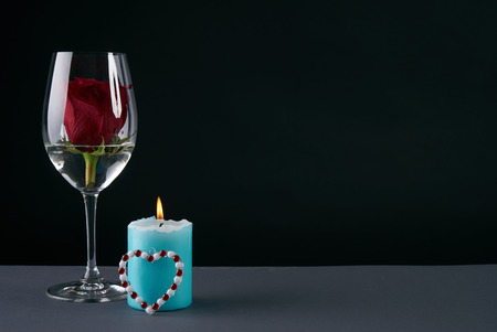 Wineglass with rosebud inside, candle and heart on dark background. Love card concept with copy space. Valentines day theme Stock Photo