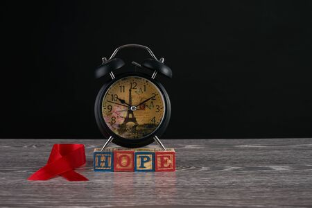 Alarm clock, red awareness ribbon and hope word on cubes with letters. Symbol of solidarity with people living with HIV AIDS. Healthcare and medicine concept