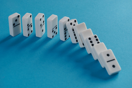 White toppling domino play pieces on blue background. Chain reaction Foto de archivo