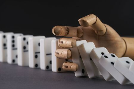 Wooden hand trying to stop toppling dominoes on table. Chain Reaction Stock Photo
