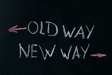 adapting: Old Way, New Way written on a blackboard with arrows pointing in the direction of the past and the future. A concept for adapting to change, improvement and development for the self or the business Stock Photo