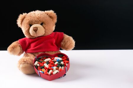 Teddy bear and heart shaped box with medicine and pills