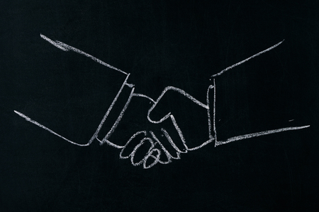 each: Business and office concept - businessman shaking hands each other.Drawn with chalk on blackboard. Stock Photo