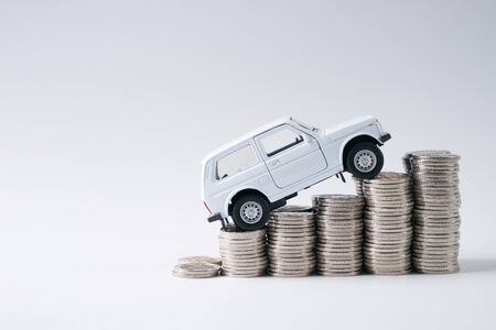 A toy white car model in top of stack of coins isolated on white background with copy space.Financial and business concept.