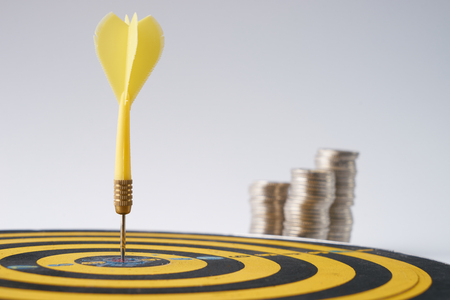 asserts: Yellow dart hit in the center of a target with stack of coins behind on white background with copy space. A idea about money  currency investment that must decide or think carefully  thoroughly before putting money in these risky assets.