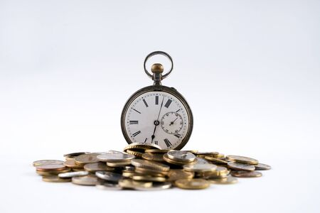spacetime: Old pocket watch with open cover on scattered coins isolated on white with copy space.Time is money concept. Stock Photo