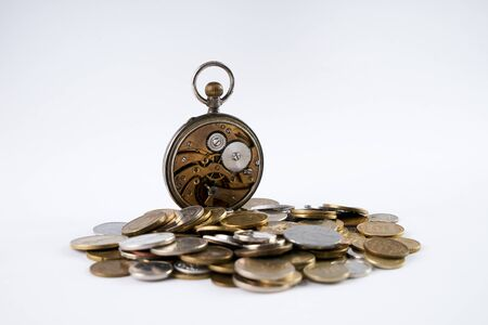monedas antiguas: Old Clockwork with open cover on scattered coins isolated on white.Time is money concept.